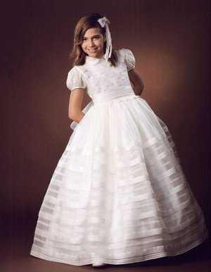 Los complementos de este vestido son un poco más típico de primera comunión. Los adornos de flores en el pelo, junto con los guantes en las manos,