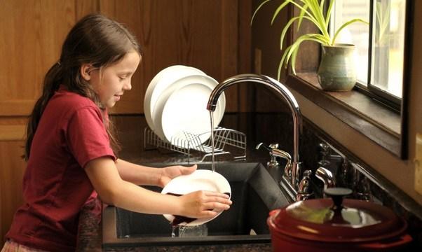 niña lavando platos